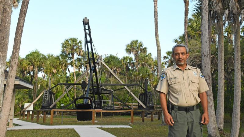 Man standing in front of a dredge machine