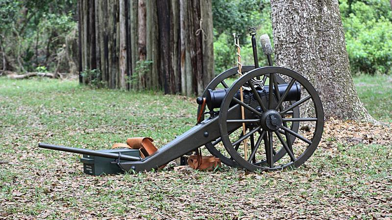 a small cannon stands next to a tree, with a picket fence in the background.