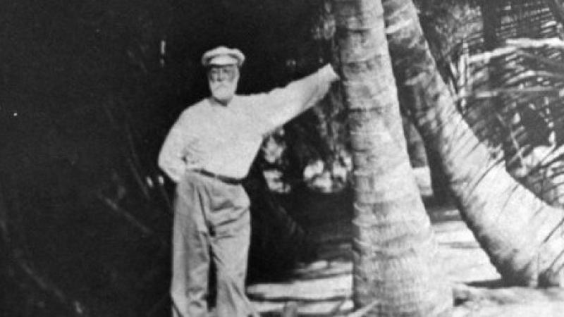 A black and white photo of a man standing next to a large tree.