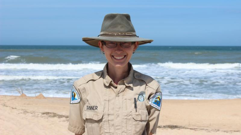 Park Ranger Jodi Tanner smiling at the camera with the ocean behind her