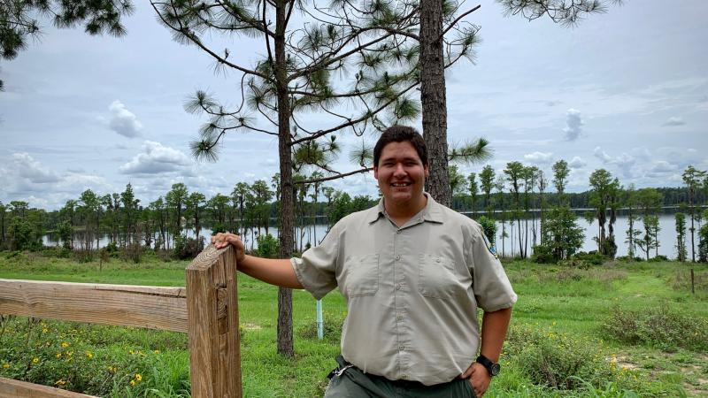 Park Ranger Sam Louzan smiling for the camera with pine trees and a lake behind him
