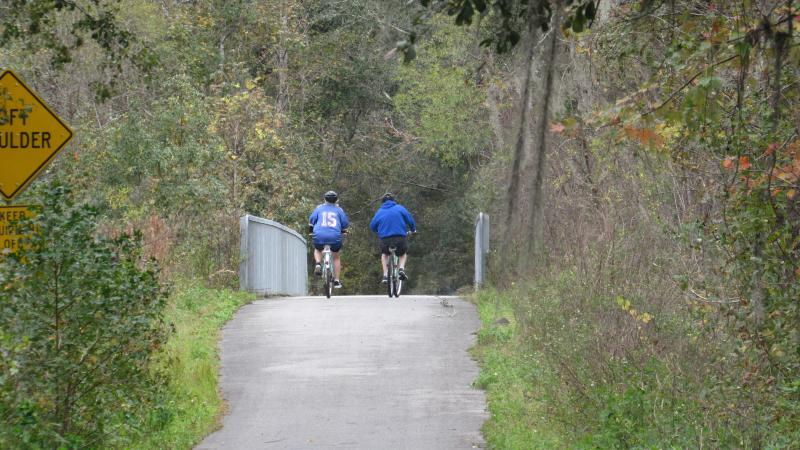 Two people on bicycles ride along a paved trail surrounded by trees.