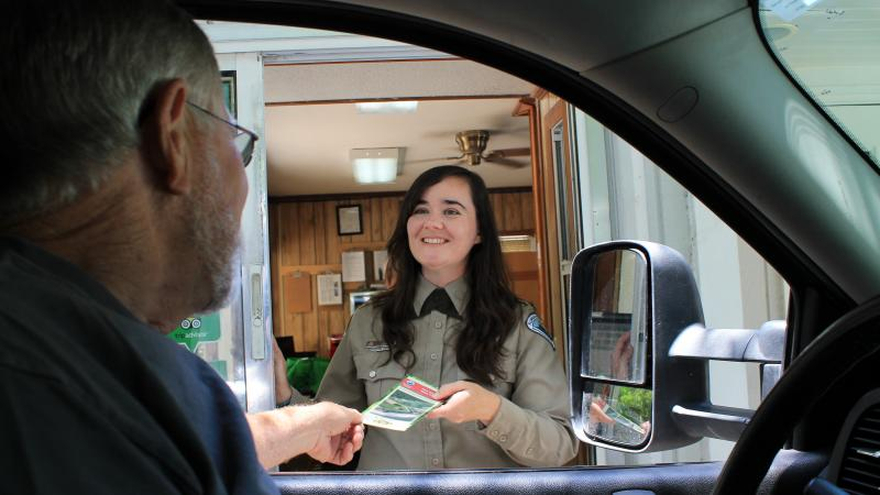 Park staff at ranger station giving visitor a brochure