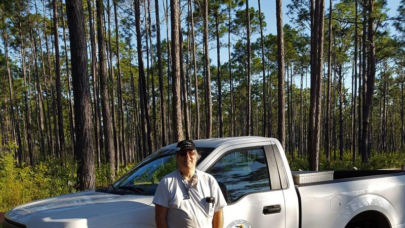 Volunteer Jeff Junior stands in front of park truck and forest of trees.