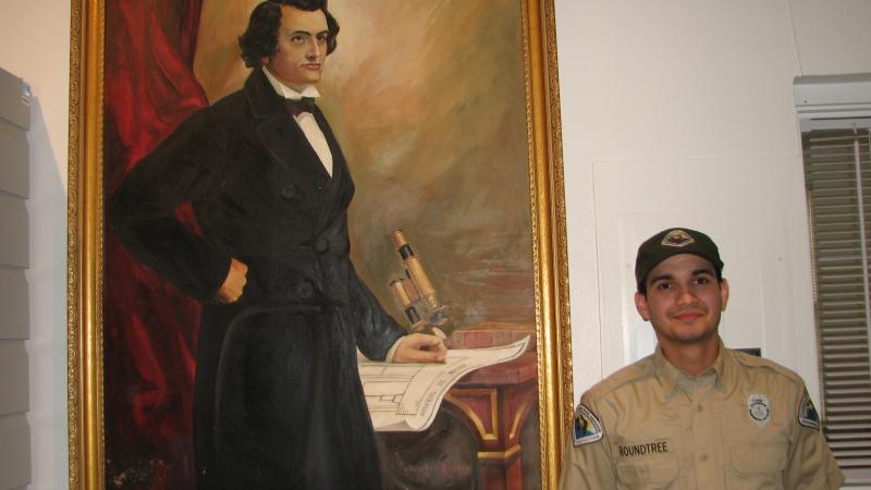 Park Ranger Jeromy Roundtree stands next to large painted portrait of John Gorrie displayed in the museum.