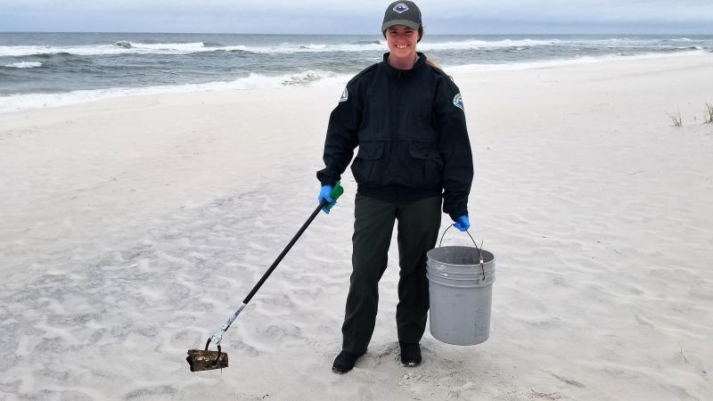 Jessica Ryan picking up trash along the beach.