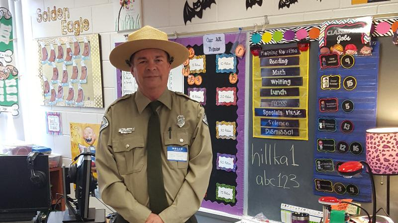 a park ranger in uniform stands in the middle of school classroom
