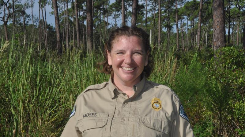 Image of Park Manager Katie Moses with background of pine trees