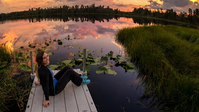 A person sitting on a dock on the edge of a lake.