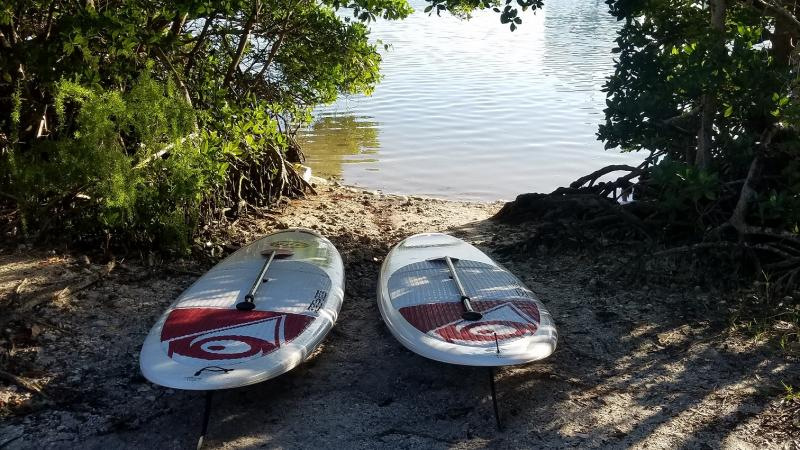 Two paddle boards at launch area by the water