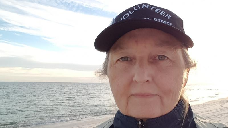 Volunteer Laura Junior proudly wears volunteer hat while walking the beach at Perdido Key.