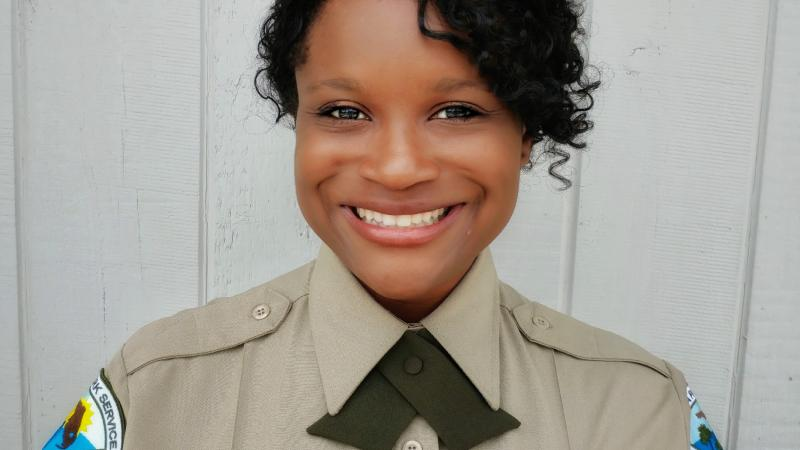Angela, wearing her ranger uniform, smiling at the camera.
