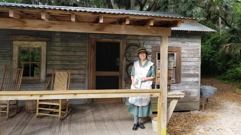 a woman in period dress stands on the porch of a wooden cabin