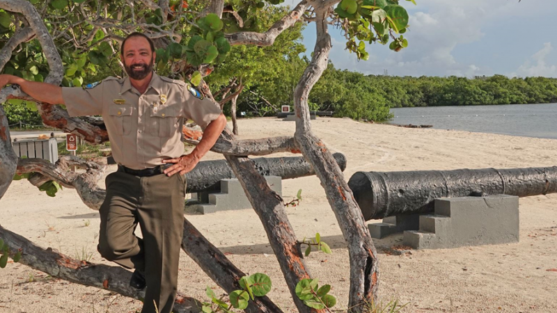 bearded man in Florida Park Service uniform, with background of beach sand, water, green mangroves, and partly cloudy blue skies