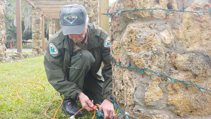 A man in a ranger uniform is bent down fixing Christmas lights.