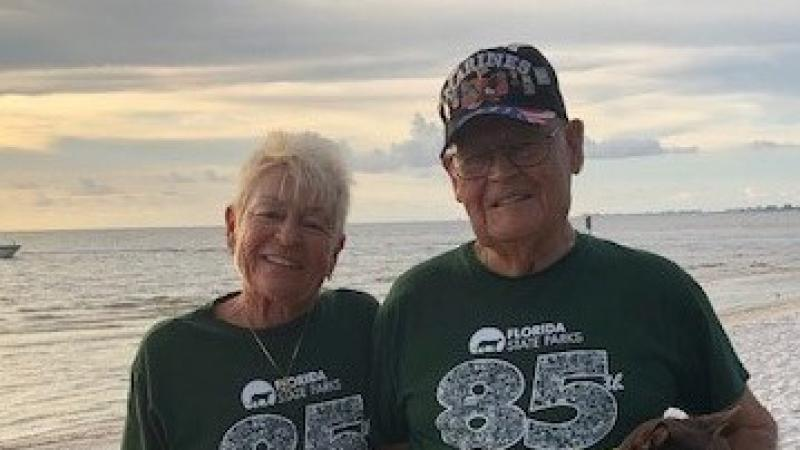 Two volunteers wearing Florida State Parks 85th Anniversary t-shirts, smiling at the camera and holding a little dog, with the beach in the background.