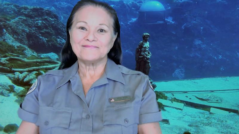 Rita King, smiling at the camera, standing in front of the underwater observatory.