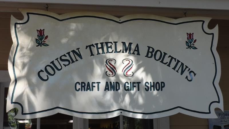 "a sign above a porch reads ""cousin thelma boltins craft and gift shop"""