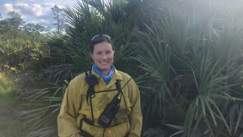 Park Ranger Sara Travis stands with native vegetation in fire gear before a burn
