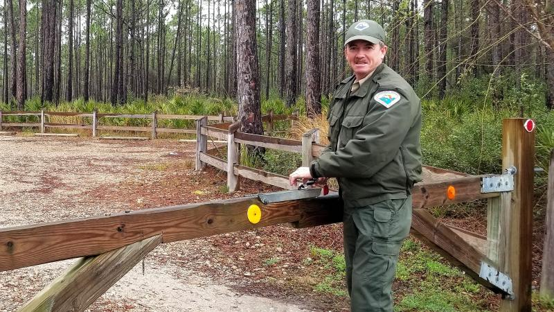 Scott Hoxie standing by a gate in his ranger uniform.