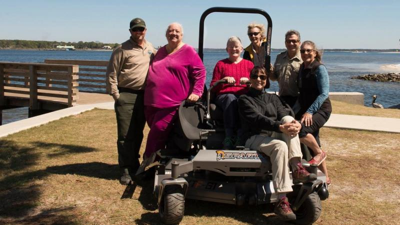 Members of the St. Andrews Friends group standing around a lawn mower.