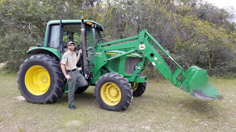 Park Ranger Kyle Blair standing next to a tractor and smiling at the camera