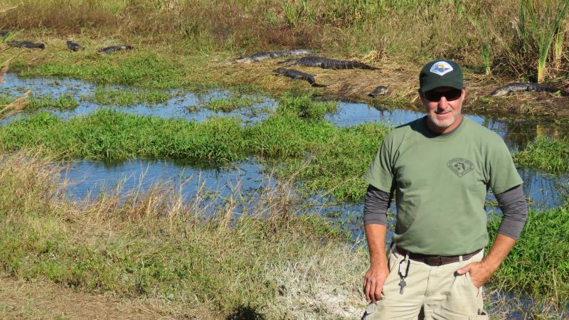 Park staff Steve Kline with alligators behind him