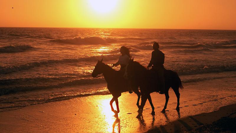 two people ride horses in the surf at sunset