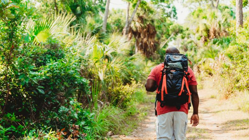 a man has his back turmed, walking on a trail with a backpack.