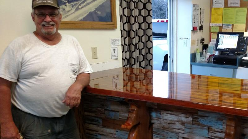 Jerry Allen smiling at the camera with his finished project at the Ranger Station