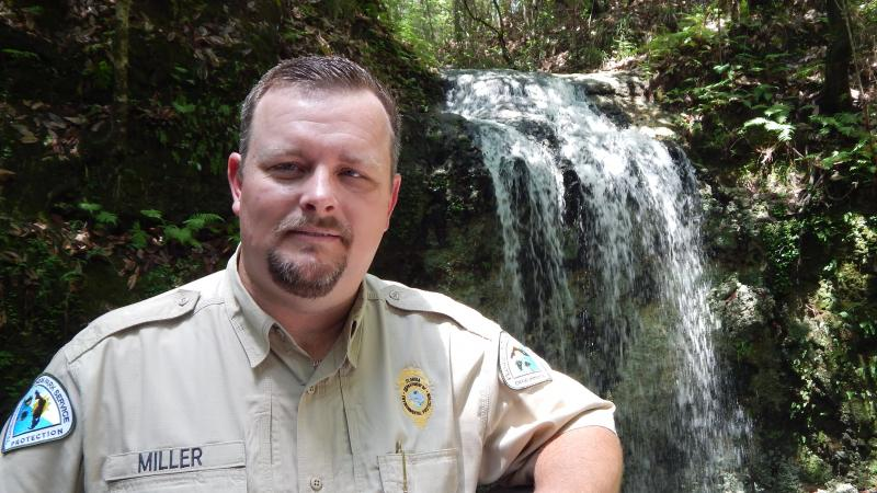 Park Manager Aaron Miller stands in front of the waterfall.