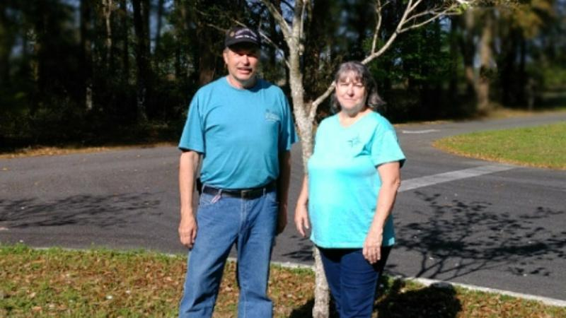 a man and woman in blue shirts stand next to a tree.