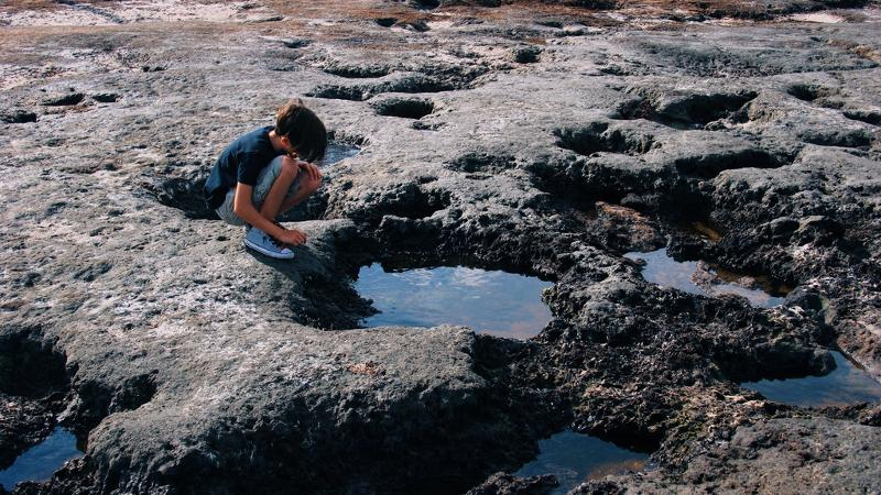 a boy crouches on the edge of a pool formed by hardened black dirt on a beach
