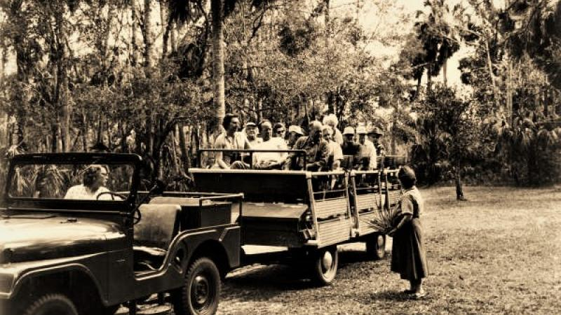 A black and white photograph shows Carol Beck speaking with visitors on a tram ride at Highlands Hammock State Park.