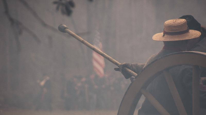 Reenactors reload cannon. US flag is visible through the smoke.