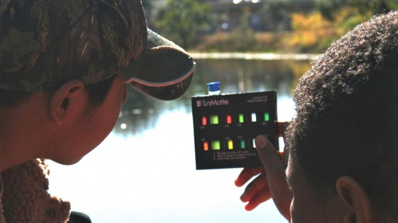 Two boys looking at a water testing device.