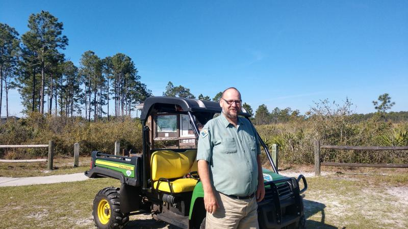 a man in uniform stands next to a golf cart