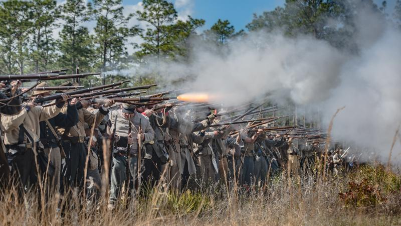 reenactors dressed as confederate soldiers stand in a long line firing guns