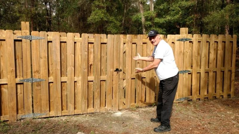 Clenn Copp, park volunteer, is seen standing next to a wooden fence at Suwanee River State Park.