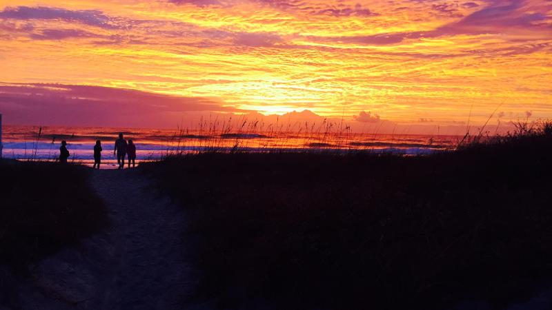 Image of four people silhouetted by the sunrise over the ocean at Little Talbot Island State Park.