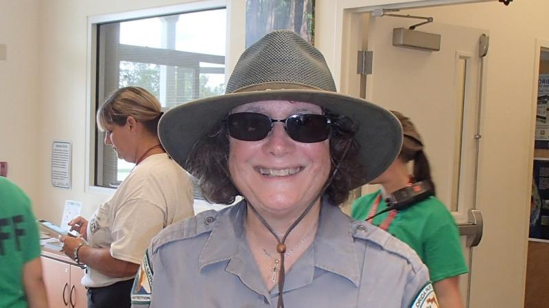 Mary Dodd, smiling at the camera, wearing her volunteer uniform.