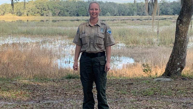a park ranger stands on a lake shore, surrounded by trees and golden grasses.