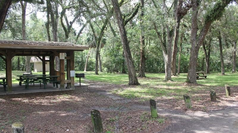 a picnic pavilion with tables sits in a lot under oak trees.
