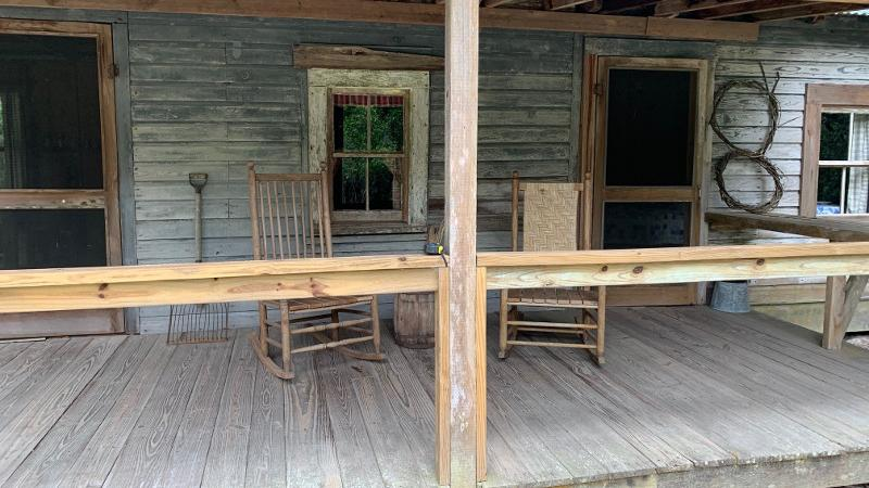 Two rocking chairs sits on the porch of a wooden cabin