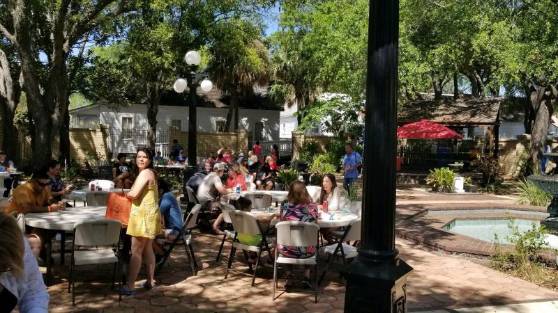 A view of people at an event in the Ybor City Museum garden.