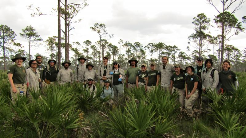 A group of FLCC members pose in a pine scrub landscape, wearing khaki and green uniforms and smiling.