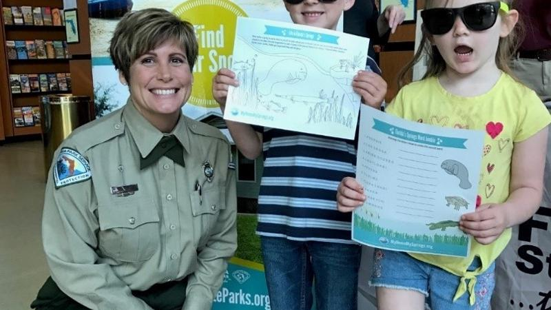 Image of Rianna Elliott, park services specialist, kneeling besides two junior rangers.