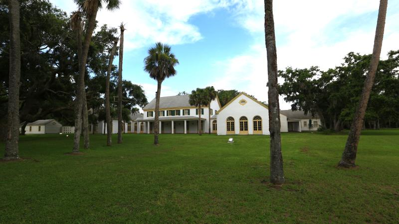 a stately house on a green lawn with palm trees