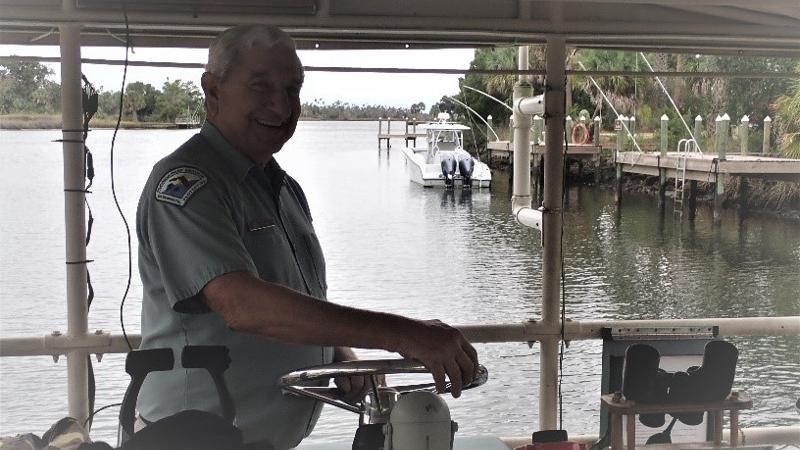 Image of Rick Mainster at the wheel of the Monroe, Crystal River state park's tour boat.