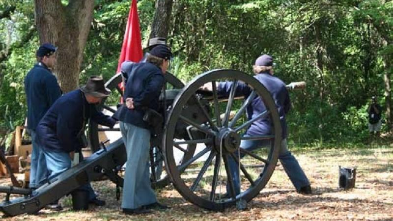 three reenactors dressed as union soldiers load a cannon